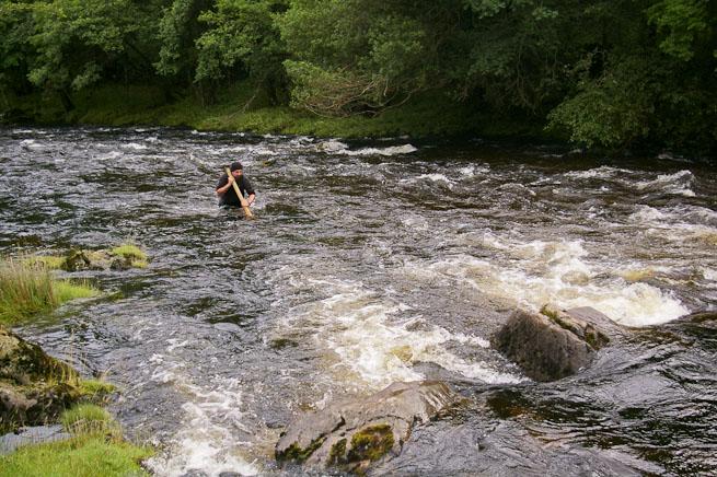 James Bath wading across a river